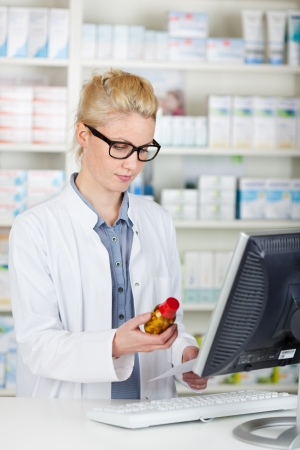 Young female pharmacist checking prescription bottle by computer at the drugstore photo