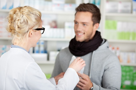 Young happy male customer buying medicine at the pharmacy photo