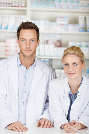 Portrait of a serious male and female pharmacists in front of medicines at drugstore photo