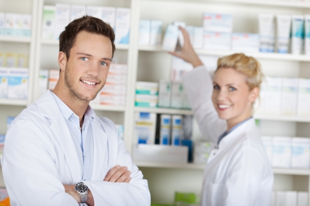 Portrait of a smiling pharmacists team smiling in front of medicines at drugstore photo