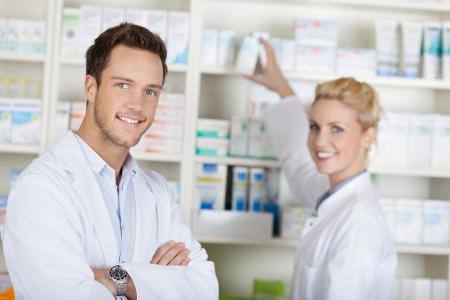 Retrato de un equipo de farmacéuticos sonriendo sonriente delante de medicamentos en farmacias Foto de archivo