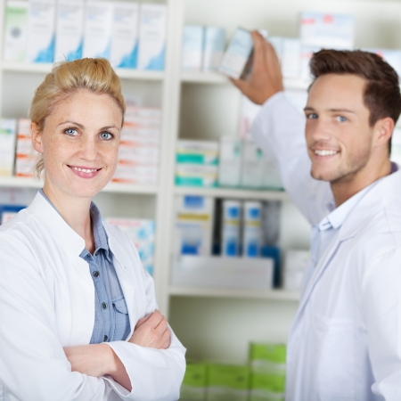 Portrait of a young male and female pharmacists smiling in front of medicines at drugstore photo