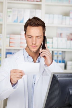 Young male pharmacist on the phone while looking at receipt at drugstore photo
