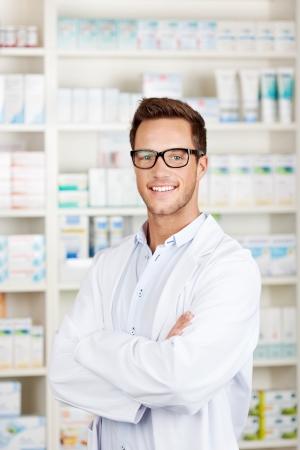 Portret van een zelfverzekerde mannelijke apotheker glimlachend voor geneesmiddelen bij drogisterij
