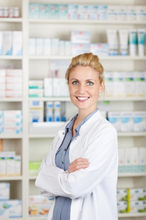 Portrait of a confident female pharmacist smiling in front of medicines at drugstore