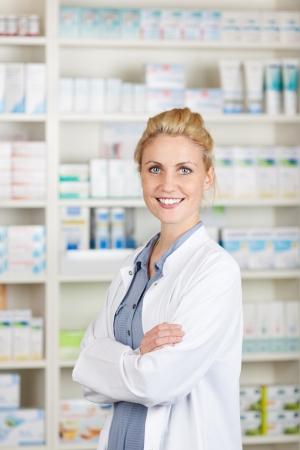 Portret van een zelfverzekerde vrouwelijke apotheker lachend voor geneesmiddelen bij drogisterij