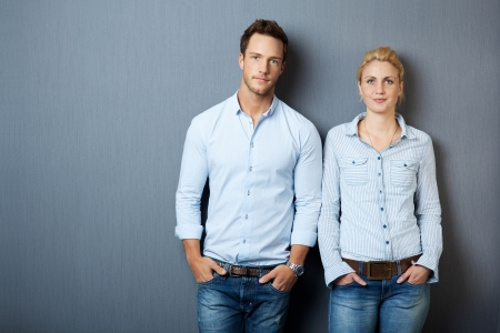 woman serious: Portrait of a serious young man and woman looking in camera and standing against gray background
