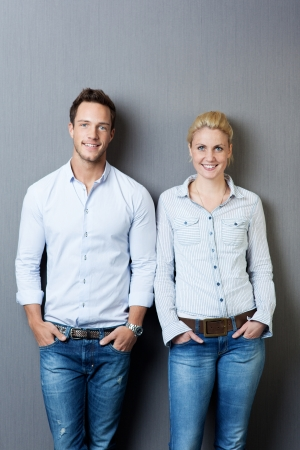 standing against: Portrait of a smart young man and woman smiling and standing against gray background Stock Photo