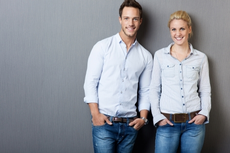 women jeans: Portrait of a smart young man and woman standing against gray background