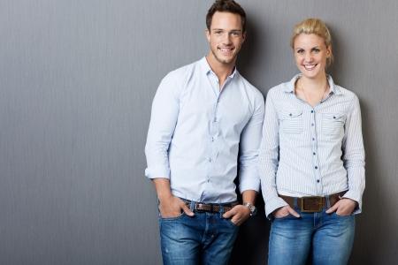Portret van een slimme jonge man en vrouw die zich tegen de grijze achtergrond Stockfoto