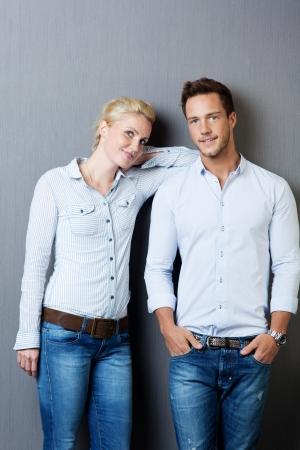 Cool jeune homme et une femme debout contre un fond gris Banque d'images - 21149375