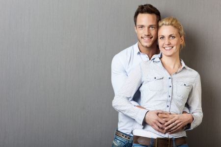 modern love: Portrait of a young happy couple standing against gray background Stock Photo