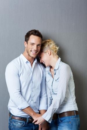 若いカップルに敵対青い背景を笑ってください。