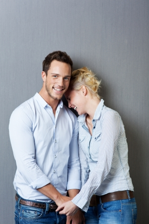Laughing young couple standing against blue background