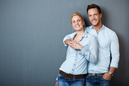 青灰色の背景に対して立っている若いカップルの肖像画