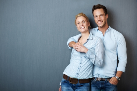 couples hug: Portrait of a young couple standing against blue gray background Stock Photo