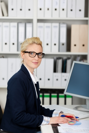 Portrait of a serious and beautiful young businesswoman wearing glasses at work photo