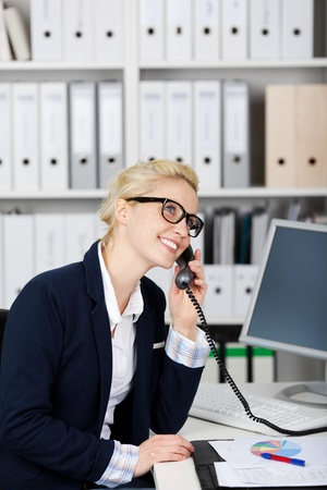 hardworking: Young smiling female executive on the phone in office Stock Photo