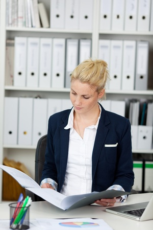 Young businesswoman reading application folder at office photo