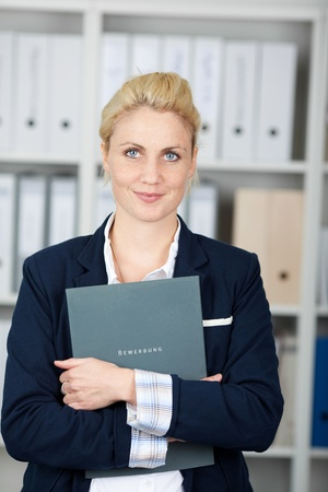 Portrait of a confident and beautiful young businesswoman with folder in the office photo