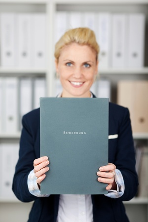 Portrait of a confident and beautiful young businesswoman holding application file in the office photo