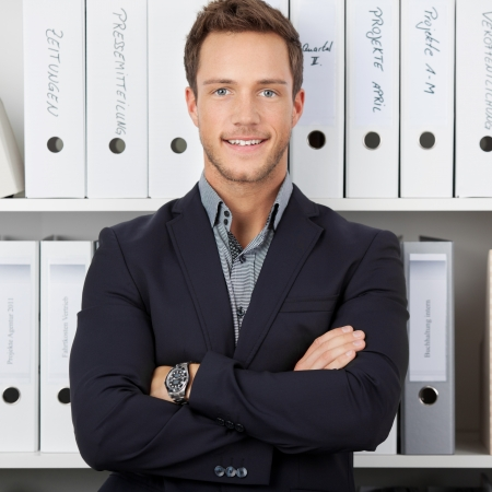 formals: Portrait of a confident young businessman standing in front of folders at office Stock Photo