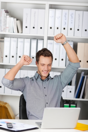 clenching fists: Happy young businessman raising hands in front of laptop at office desk
