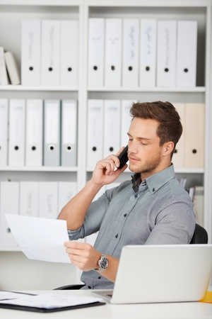 Young serious male executive on the phone looking at document in office photo