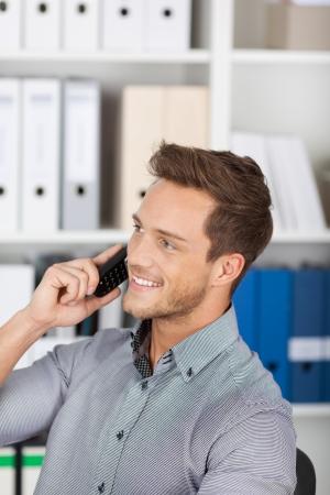 Joven ejecutivo masculina sonriente en el teléfono en la oficina