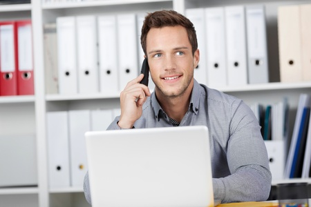 customer facing: Young smiling businessman on the phone in office