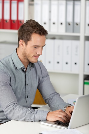 Side view of a young businessman using laptop at office desk photo