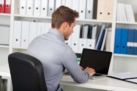 man behind: Rear view of a young businessman using laptop at office desk