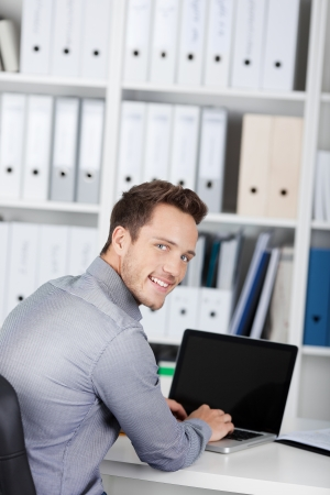 Portrait of a smiling young businessman using laptop at office desk photo