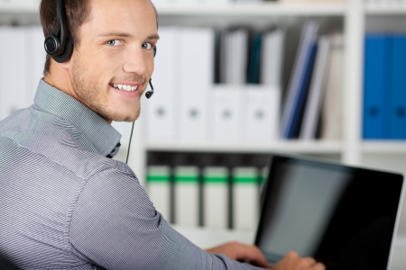 Closeup portrait of a smiling young man with headset in the office