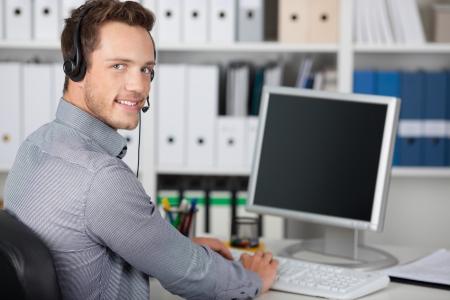 사무실에서 헤드셋 웃는 젊은 남자의 초상화