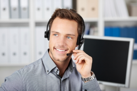 complaints: Closeup portrait of a smart smiling young man with headset in the office Stock Photo