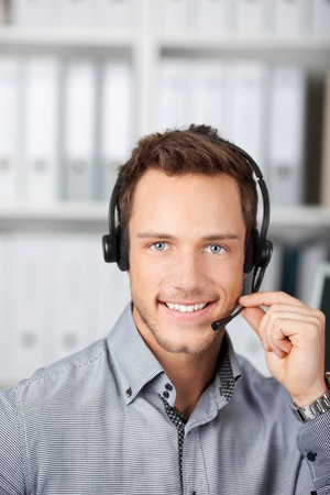 Closeup portrait of a smart young man with headset in the office