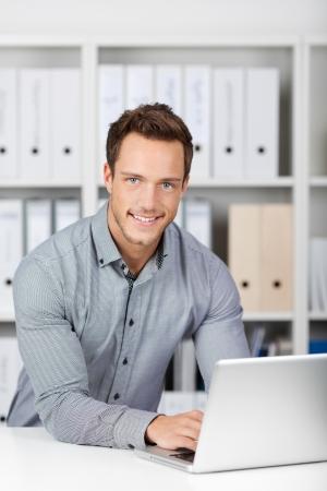 Retrato de un joven hombre de negocios con ordenador portátil sentado en la oficina escritorio Foto de archivo - 21149477