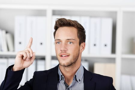 imaginative: Closeup of a young male executive pointing upwards in the office