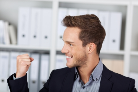clenching fists: Successful young businessman clenching fist at the office