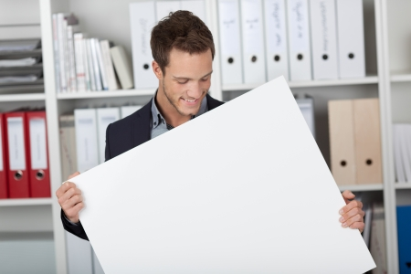 man behind: Portrait of a smiling young businessman looking at blank sign at the office