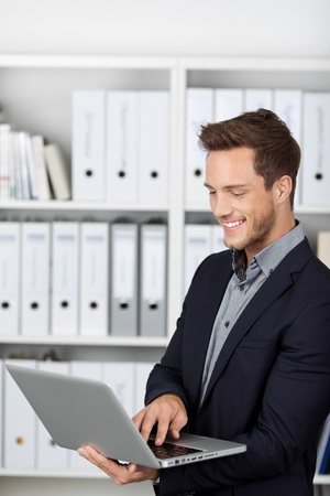 Smiling young businessman using laptop in the office photo