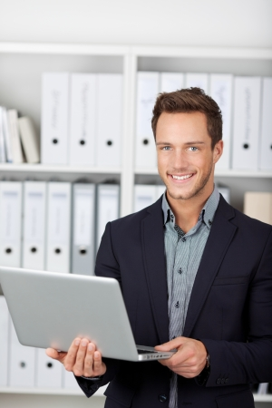 Smiling young businessman with laptop in the office photo