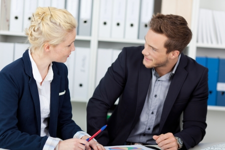 formals: Young businessman and woman in meeting at office desk