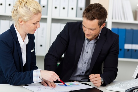 concentrating: Portrait of a smart young businessteam looking at graphs sitting at office desk