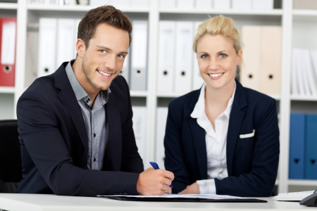 young executives: Portrait of a smiling young businessman and woman sitting at office desk