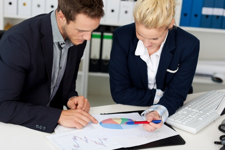 Portrait of a smart young businessman and woman looking at graphs sitting by computer at office desk photo