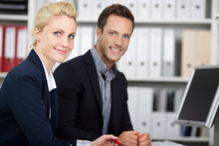 formals: Portrait of smiling young businessman and woman at office desk Stock Photo