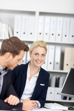 Young businessman and blond businesswoman in meeting at office desk Stock Photo - 21149508