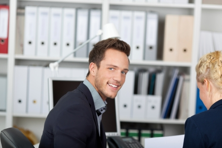 Portrait of a young smiling businessman in meeting at office desk Stock Photo - 21149509